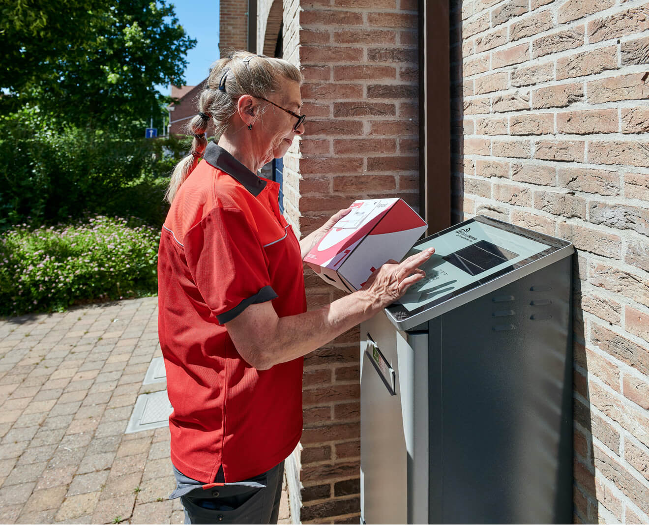 A Bpost courier delivers a parcel in a ParcelHome